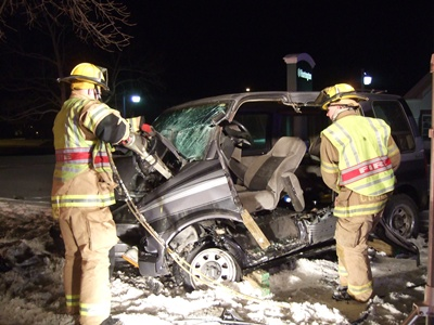 Firefighters using machinery to open a wrecked car
